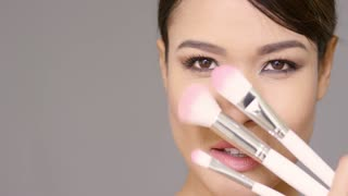 Close up on cute young lady holding three different sized makeup brushes next to her face
