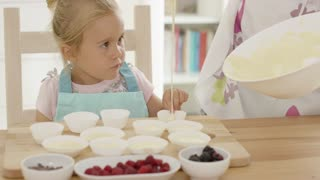 Close up on laughing girl with muffin cups as parent in floral patterned apron pours batter over her finger