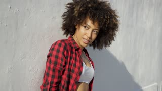 Close up portrait of african american beautiful girl. She leaning on the white concrete wall. Huge afro haircut on her head. Looking at camera.
