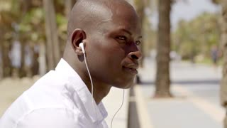 Close up side view of man with ear buds in white