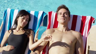 Contented young couple smiling as they sunbathe in deck chairs in the hot tropical sun alongside a pool on summer vacation