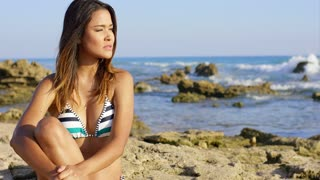 Contented young woman in a bikini sitting daydreaming on a rocky coastline in evening light looking to the side with a pensive expression