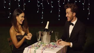 Couple celebrates with champagne in bucket and pastel colored streamers on their restaurant dinner table