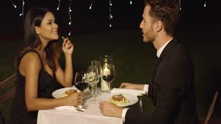 Couple eats spaghetti at fancy outdoor restaurant at night while lights hang overhead