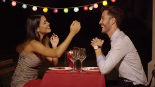 Couple holds hands across table and smiles while casually dressed for a night time dinner date
