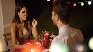Couple laughs as they raise their red wine glasses while on a night time date in fancy outdoor restaurant on Valentines day