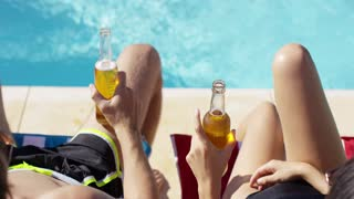 Couple relaxing at the pool with beers enjoying their summer vacation close up view of their hands and the full bottles
