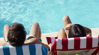 Couple relaxing in colorful deck chairs at the pool enjoying the hot summer sun view from the rear with just their head visible