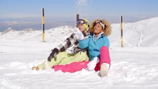 Couple sitting in snow on ski slope