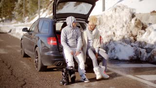 Couple talking as they put on skiing boots
