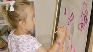 Creative little blond girl painting in a playroom sitting in front of a sheet of paper on an easel applying colorful water color paints