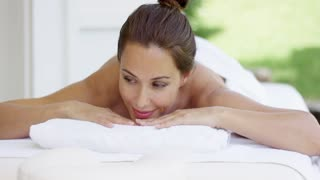 Curious woman on spa table wrapped in white towels looks to one side while resting her chin on her hands