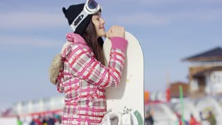 Cute asian female snowboarder relaxing on ski slope. She standing with her board and smiling to the camera. Wearing pink outfit and goggles.