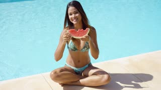 Cute bikini clad smiling woman in bikini top at edge of clear blue pool holding a partially eaten watermelon slice