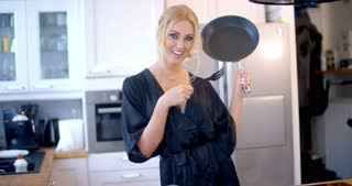 Cute blond woman cooking in the kitchen