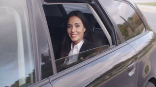 Cute business woman sitting in car waving hand