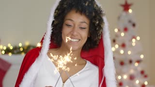 Cute friendly young woman celebrating Christmas in a festive red Santa cloak holding two burning sparklers in her hands in front of the tree