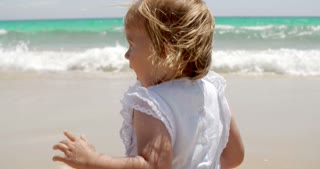 Cute little blond girl enjoying the beach