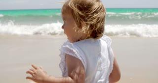 Cute little blond girl enjoying the beach