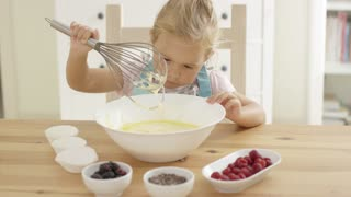 Cute little blond girl looking at muffin batter dripping from large metal with whisk in bowl with other ingredients around it