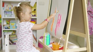 Cute little blond girl sitting indoors at home painting a colorful picture on a sheet of paper attached to an easel in a creativity concept
