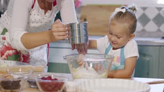 Cute little girl helping her mother bake a tart with assorted fresh berries watching as she adds flour to the mixing bowl