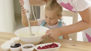 Cute little girl learning to bake from mother as she holds onto the electric whisk while mixing ingredients in a bowl