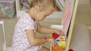 Cute little girl mixing paints on a plastic artists palette for her colorful abstract painting hanging from an easel