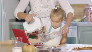 Cute little kitchen helper helping her Mum with the baking watching as she whisks cream in a mixing bowl for the topping of a fresh berry pie.