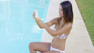 Cute playful young woman in a bikini posing for a selfie on her mobile phone as she sits dangling her feet in the water of a swimming pool.