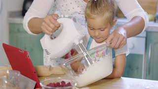 Cute pretty little girl watching her mother whisk cream as they bake a fresh berry tart together in the kitchen close up view of the child.