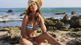 Cute pretty young woman in a bikini and straw sunhat sitting on a rocky shoreline in the beach sand smiling at the camera