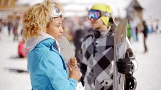 Cute woman holding snowboard on ski slope
