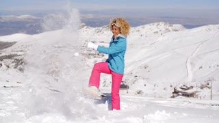 Cute woman in skiing clothes kicking snow