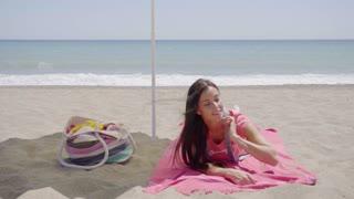 Cute woman laying down on beach blanket