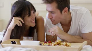 Cute young newlywed couple playing with food while having breakfast in bed with tray of pastries and bowl of fruit