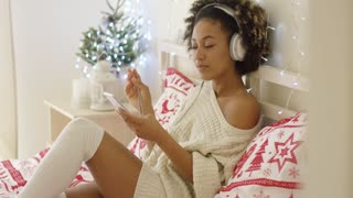 Cute young woman enjoying her music at Xmas lying on her bed in a stylish winter outfit on a Christmas duvet grinning as she listens to the tunes.