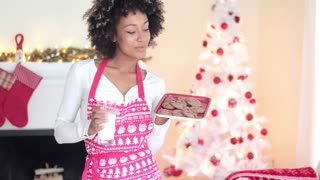 Cute young woman in a festive red apron standing in front of the Christmas tree holding milk and cookies for Santa
