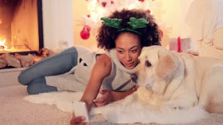 Cute young woman wearing a colorful green set of Christmas reindeer antlers taking a selfie with her dog as they relax in the living room in front of the fire.