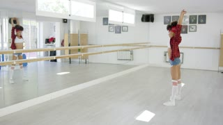 Dancing student performs in bright studio in front of wall covered in mirror panels