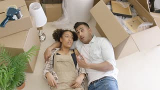 Dreaming and happy young mixed race couple lying on the floor among unpacked carton boxes in their new apartment.