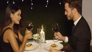 Elegant attractive young couple sipping red wine during a romantic dinner at a nightclub or restaurant