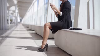 Elegant businesswoman reading her text messages