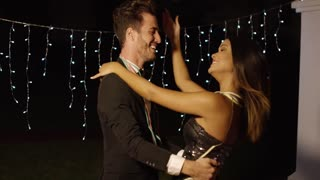 Elegant young couple dancing at night against twinkling strings of lights with focus to a gorgeous young woman with a dreamy expression