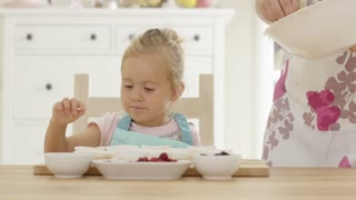 Excited child pointing as unidentifiable parent pouring muffin batter into holders in kitchen