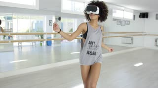 Excited female dancer with VR goggles on eyes. She practicing her dance in Virtual Reality world.