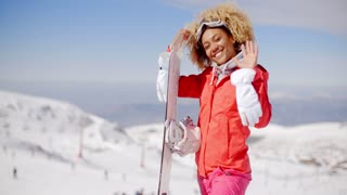 Excited skier waving from top of slope