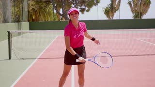 Excited young woman player running across a tennis court with her racket in her hand and a beaming smile towards the camera