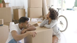 Exhausted couple taking a break from packing their household goods into boxes to move home