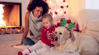 Family Christmas celebration next to fireplace with a young african american woman relaxing with grinning young little girl and labrador dog on the floor in front of a blazing fire and decorated tree.